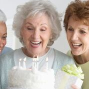 Woman and sisters and birthday cake