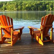 Adirondak chairs on deck at lake